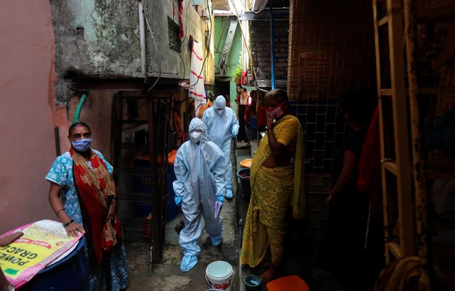 Health workers walk in a lane during a free medical camp in Dharavi, one of Asia's largest slums in Mumbai, India, Saturday, June 20, 2020. India is the fourth hardest-hit country by the COVID-19 pandemic in the world after the U.S., Russia and Brazil. (Photo by Rafiq Maqbool/AP Photo)