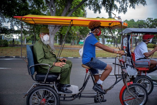 A man wearing a military uniform in the back of a bicycle taxi rides with a group around Havana, Cuba, playing music from a speaker to mark May Day, or International Workers' Day, Friday, May 1, 2020. Due to the coronavirus pandemic, the Cuban government called off May Day celebrations, an event that showcases a huge rally and march in Revolution Square. (Photo by Ramon Espinosa/AP Photo)