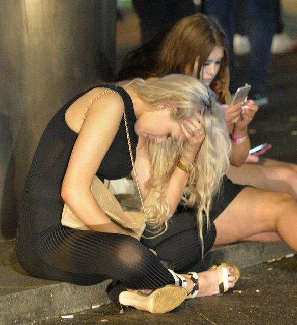 A partygoer holds her head in her hands while her friend plays on her phone . Mayhem hits the streets of Newcastle, UK as clubbers out on the Toon have a little too much to drink as they enjoy the Bank Holiday on August 29, 2016. Photographs take last night show scantily-clad women passed out on the pavement, while boozed-up men were caught arguing with police. (Photo by XposurePhotos.com)