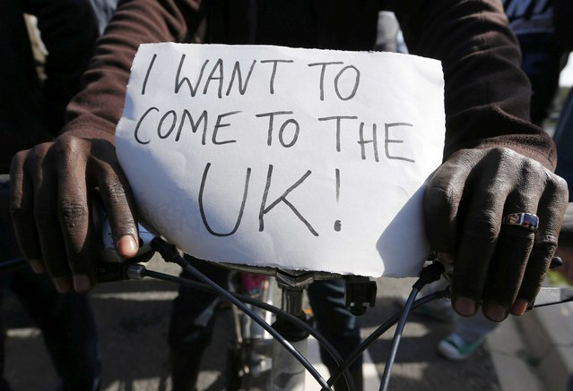 "A migrant holds a placard which reads ""I want to come to the U.K."" on his bicycle at the makeshift camp called ""The New Jungle"" in Calais, France, September 19, 2015. (Photo by Regis Duvignau/Reuters)"