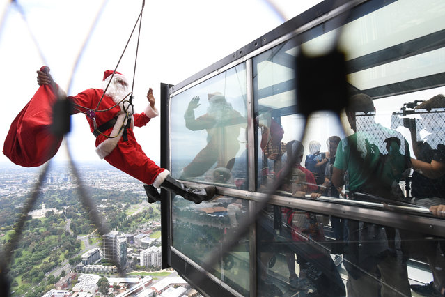 A stuntman dressed as Santa Claus greets visitors to the Eureka Skydeck observation point, on the 88th floor of the Eureka Tower in Melbourne, Australia on December 10, 2017. (Photo by James Ross/AAP)