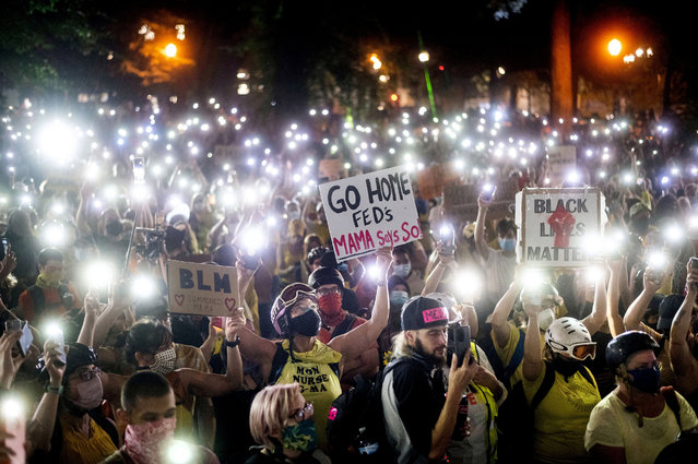Hundreds of Black Lives Matter protesters hold their phones aloft on Monday, July 20, 2020, in Portland, Ore.  Federal officers' actions at protests in Oregon's largest city, hailed by President Donald Trump but done without local consent, are raising the prospect of a constitutional crisis – one that could escalate as weeks of demonstrations find renewed focus in clashes with camouflaged, unidentified agents outside Portland's U.S. courthouse. (AP Photo/Noah Berger)