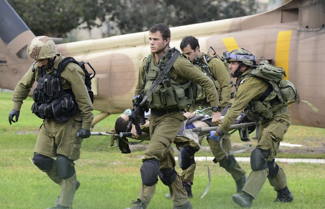 Israeli soldiers carry a comrade who was wounded in an attack on the border with Egypt to a hospital in Beersheba, Israel, Wednesday, October 22, 2014. Attackers from the Egyptian side of the border fired an anti-tank missile and gunshots at an Israeli military vehicle on Wednesday, wounding two soldiers in a rare cross-border incident,  the Israeli military said. The Israeli military said it has no indication yet who was behind the attack. (Photo by Dudu Grunshpan/AP Photo)