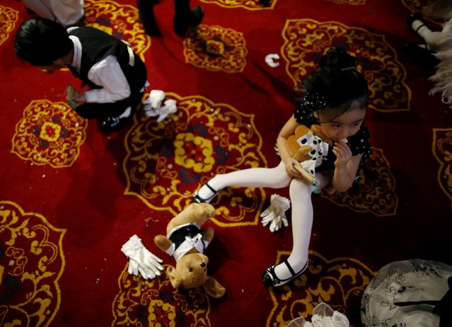 A child model eats a biscuit on the floor of the backstage during a rehearsal for the Dong Wenmei T100 Children's Collection during China Fashion Week in Beijing October 29, 2014. (Photo by Kim Kyung-Hoon/Reuters)