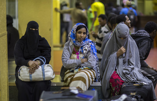 In this photo taken Friday, December 22, 2017, Ethiopian women sit on a luggage conveyor belt as they wait for family members after being deported from Saudi Arabia, at the airport in Addis Ababa, Ethiopia. Undocumented Ethiopian migrants who are being forcibly deported from Saudi Arabia by the thousands in a new crackdown say they were mistreated by authorities while detained. (Photo by Mulugeta Ayene/AP Photo)