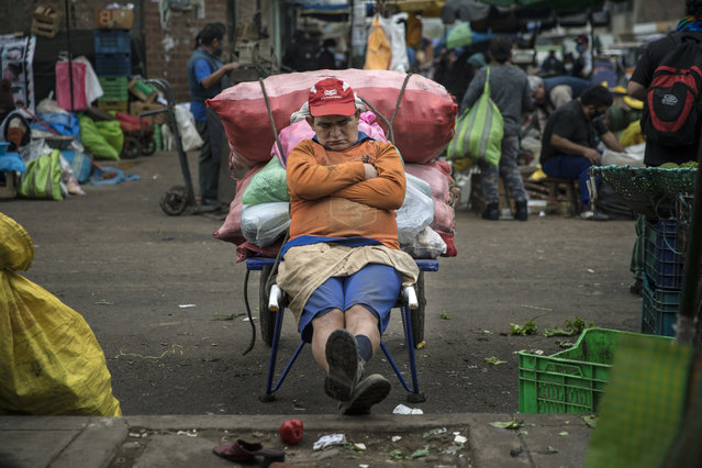 Porter Fernando Anaya, who begins his workday at 4 a.m., takes a nap as he takes a break from transporting vegetables, in La Parada market in La Victoria district, in Lima, Peru, Tuesday, June 23, 2020. With hundreds of millions relying on such markets for their food and livelihoods, officials are debating whether and how they can operate safely amid the new coronavirus pandemic. (Photo by Rodrigo Abd/AP Photo)