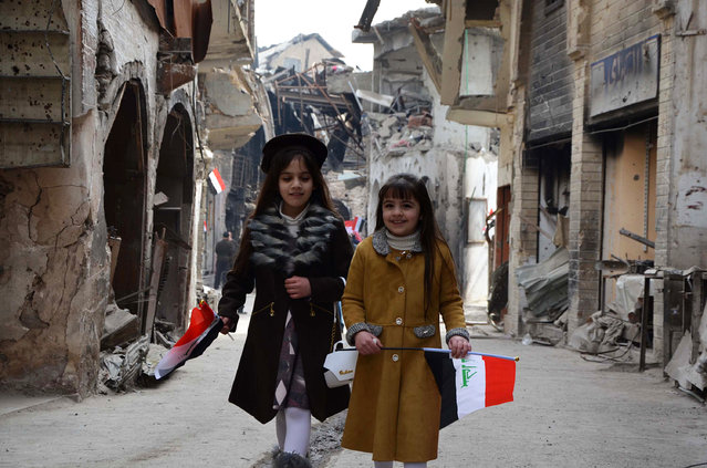 Iraqi girls walk holding their national flag towards a ceremony for the re-opening of the Bab al-Saray market in the old city of Mosul on January 11, 2018. (Photo by Ahmad Muwafaq/AFP Photo)