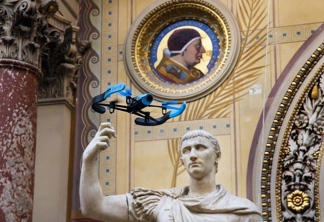 "The new Bebop Parrot drone flies front of a Rome marble statue ""August en Triomphateur"" during a presentation to the press in Paris, France, Friday, November 7, 2014. The new Parrot Bebop drone, a quadcopter type drone with a fish eye camera benefits from an exclusive 3-axes image stabilization system that maintains a fixed angle of the view, regardless of the inclination of the drone and its movements caused by wind turbulence. (Photo by Francois Mori/AP Photo)"