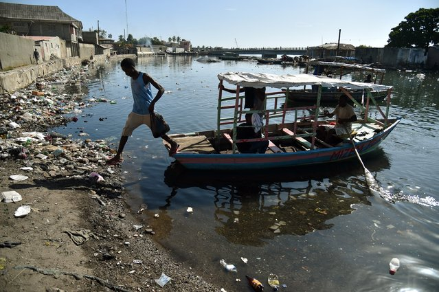 A man jump fron a boat in Mapou River in Cap-Haitien, Haiti, on September 6, 2017. (Photo by Hector Retamal/AFP Photo)