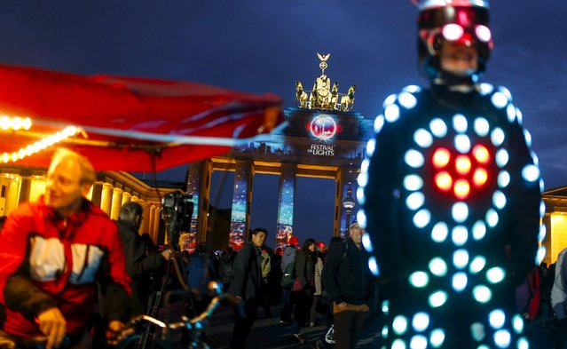 "People look at a light installation at the Brandenburg Gate during the opening day of the ""Festival of Light"" show in Berlin, Germany, October 9, 2015. (Photo by Hannibal Hanschke/Reuters)"