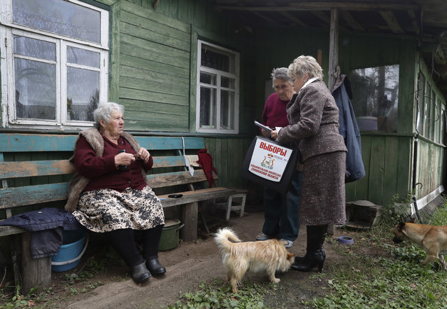 An election commission official talks with voters, outside their home in the village of Gusino, outside Smolensk, western Russia, Sunday, September 18, 2016. Russia's governing party and its three largely cooperative opponents are expected to retain their positions in the national parliament, but new procedures for choosing the seats could affect their proportions. (Photo by Sergei Grits/AP Photo)