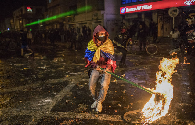 Demonstrators clash with police during protests sparked by the death of a man after he was detained by police in Bogota, Wednesday, September 9, 2020. Javier Humberto Ordonez, 46, died in hospital after receiving repeated electric shocks with a stun gun from officers who detained him for violating social distancing rules to curb the spread of the coronavirus. (Photo by Ivan Valencia/AP Photo)