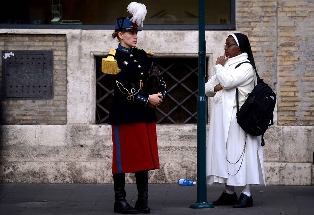 A member of a military band (L) and a nun wait at a bus stop in Rome on November 11, 2014. (Photo by Filippo Monteforte/AFP Photo)