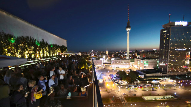 """People chat on the rooftop bar at the club """"House of the Weekend"""" at Alexanderplatz square in Berlin, Germany, August 24, 2016. Hannibal Hanschke: """"The terrace of Weekend beside the TV tower feels like real Berlin. High above the streets, it's a perfect place to catch the sunset"""". (Photo by Hannibal Hanschke/Reuters)"""