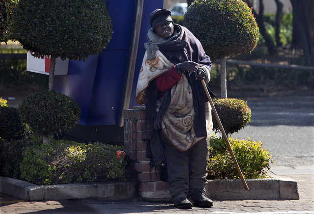 A homeless man stands at a street corner in Johannesburg, Wednesday July 22, 2020. Official statistics show that South Africa's economy has sunk deeper into recession, with its gross domestic product for the second quarter of 2020 plummeting by 51%, largely as a result of COVID-19 and the country's strict lockdown. (Photo by Denis Farrell/AP Photo)