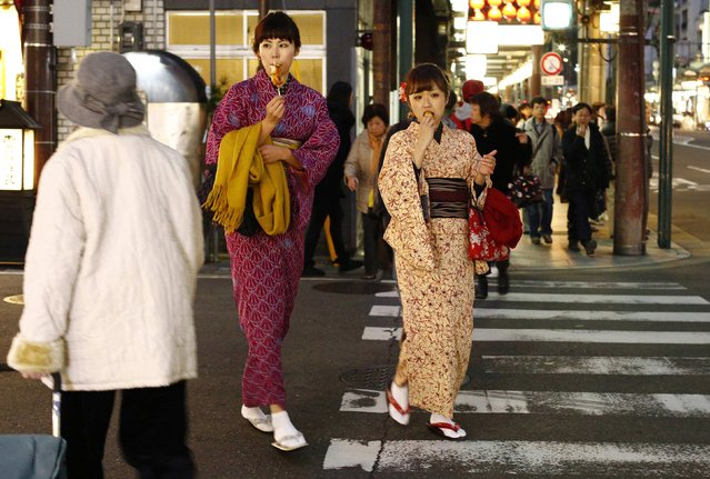 Women, dressed in traditional Japanese kimonos, cross a street in Kyoto, western Japan November 19, 2014. (Photo by Thomas Peter/Reuters)