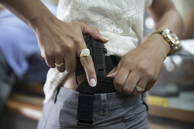 An Israeli woman checks out a new pistol at a gun shop in Tel Aviv October 20, 2015. A growing number of Israelis are attending self defence classes, learning how to protect themselves from knife attacks, as the country has seen near-daily stabbings and shootings by Palestinians and Israeli-Arabs. Many people have also rushed to gun shops and shooting ranges to get a weapon or renew their existing gun license. (Photo by Baz Ratner/Reuters)