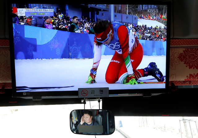 A bus driver is reflected in a mirror while the biathlon is broadcast on television in Pyeongchang, South Korea, February 15, 2018. (Photo by Eric Gaillard/Reuters)