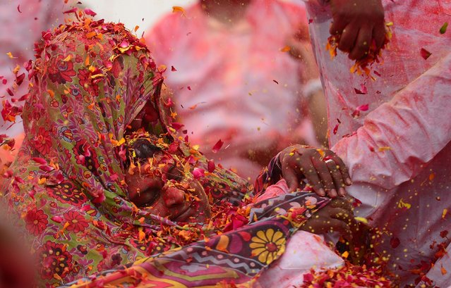 Flower petals and coloured powder is thrown around at an event to celebrate the Hindu festival of Holi for children with cerebral palsy organized by the Trishla Foundation in Allahabad, India on February 25, 2018. (Photo by Sanjay Kanojia/AFP Photo)