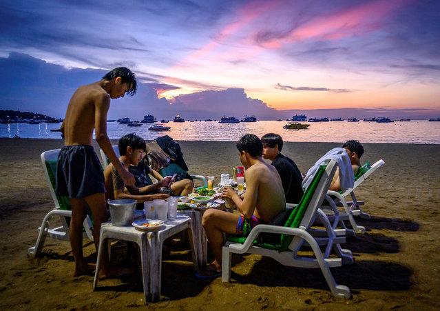 Men eat dinner on the empty Pattaya beach, Thailand on the evening of September 1, 2020. (Photo by Mladen Antonov/AFP Photo)