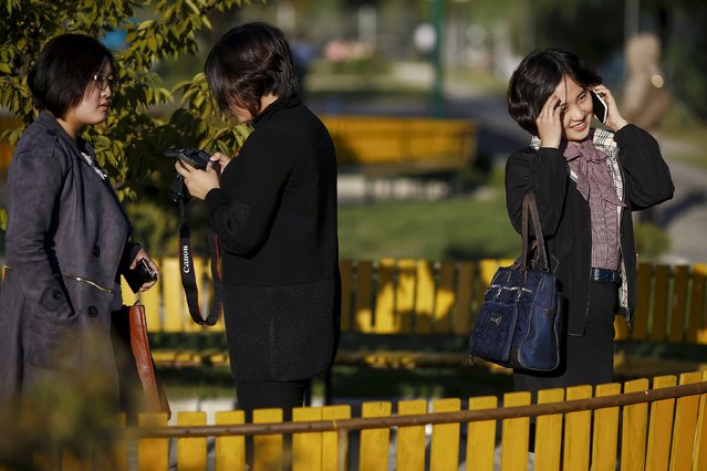 Girls enjoy nice weather at a park in front of the Pothonggang Department Store in central Pyongyang October 11, 2015. (Photo by Damir Sagolj/Reuters)