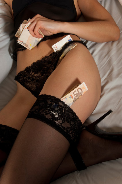 Some fifty euro banknotes were on thighs and buttocks and inserted in the stockings of a girl wearing lingerie and high heels lying on the bed. (Photo by Maurizio Milanesio/Getty Images/iStockphoto)
