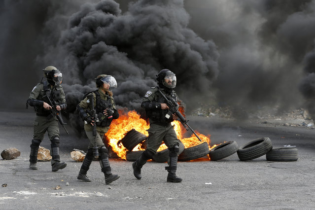 Israeli border guards advance down a street during clashes with Palestinian protesters following a demonstration in the West Bank city of Ramallah on March 9, 2018 against a decision by US President Donald Trump to recognise Jerusalem as the capital of Israel. (Photo by Abbas Momani/AFP Photo)