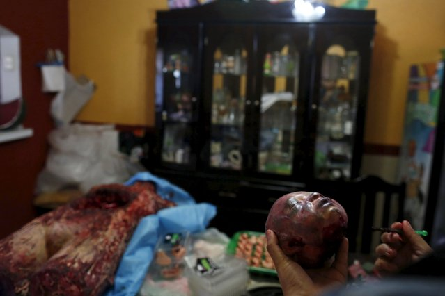 A woman works on the details of a bloody zombie baby head made of gummy candy at the Zombie Gourmet homemade candy manufacturer on the outskirts of Mexico City October 30, 2015. (Photo by Carlos Jasso/Reuters)