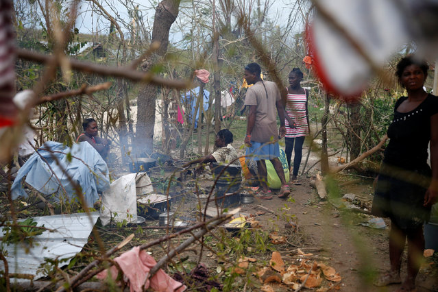 People cook their meal next to fallen trees after Hurricane Matthew passes Jeremie, Haiti, October 5, 2016. (Photo by Carlos Garcia Rawlins/Reuters)