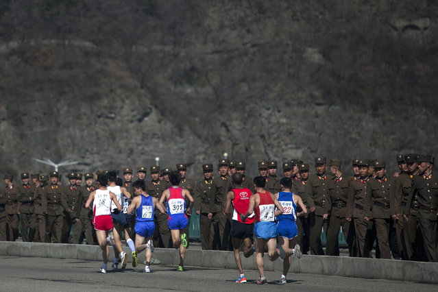 Marathon runners pass by a long row of North Korean soldiers as they cross a bridge in Pyongyang on Sunday, April 14, 2013. North Korea hosted the 26th Mangyongdae Prize Marathon to mark the upcoming April 15, 2013 birthday of the late leader Kim Il Sung. (Photo by David Guttenfelder/AP Photo)