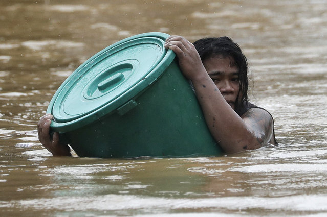 A resident uses a plastic container as a floater while negotiating rising floodwaters in Marikina, Philippines due to Typhoon Vamco on Thursday, November 12, 2020. (Photo by Aaron Favila/AP Photo)