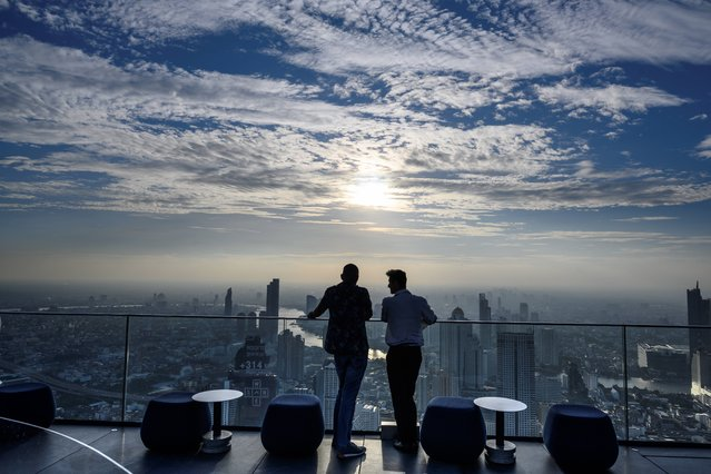Two men enjoy the city skyline view on the 314-meter high rooftop terrace of the Mahanakhon building in Bangkok on November 11, 2020. (Photo by Mladen Antonov/AFP Photo)