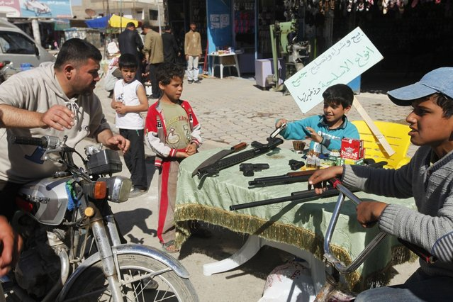 """A child mans a roadside stall with weapons and ammunition displayed for sale in the souk of Raqqa province in east Syria April 24, 2013. The placard reads: """"Selling, buying and repairing all kinds of weapons and ammunition"""". (Photo by Hamid Khatib/Reuters)"""