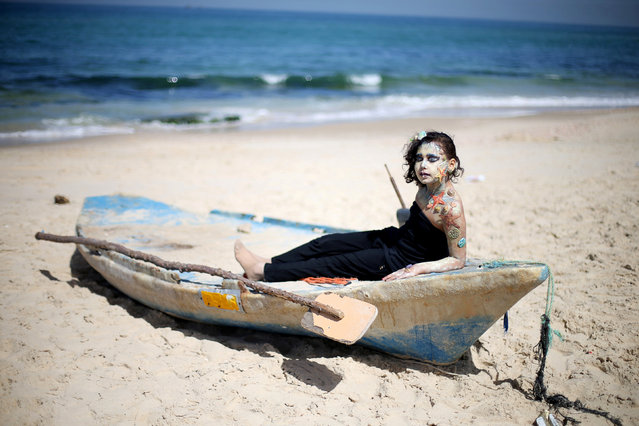 A Palestinian girl with her body painted by special effects makeup artist Alaa Abu Mustafa, 20, sits on a boat in the southern Gaza Strip, March 22, 2018. (Photo by Ibraheem Abu Mustafa/Reuters)