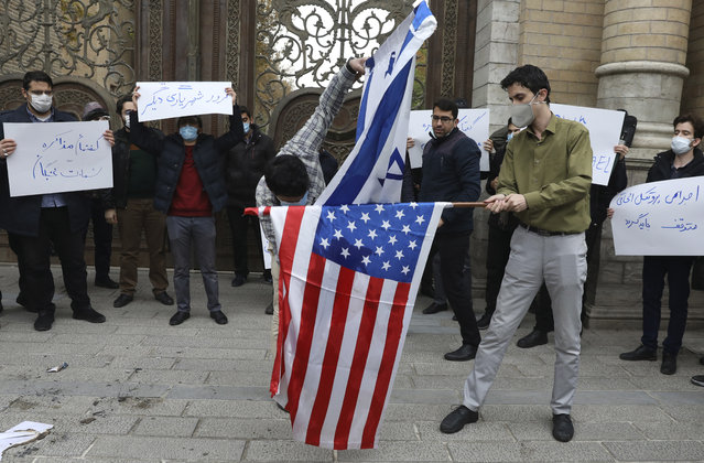 """Two protesters burn the representation of the U.S. and Israeli flags as the others hold placards condemning inspections by the UN nuclear agency (IAEA) on Iran's nuclear activities and the country's nuclear talks with world powers during a gathering in front of Iranian Foreign Ministry on Saturday, November 28, 2020 in Tehran.  Supreme Leader Ayatollah Ali Khamenei is calling for """"definitive punishment"""" of those behind killing of Mohsen Fakhrizadeh, the scientist linked to Tehran's disbanded military nuclear program. (Photo by Vahid Salemi/AP Photo)"""
