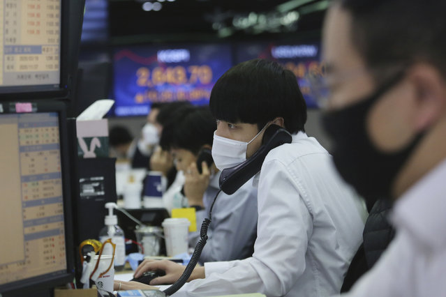 A currency trader watches monitors at the foreign exchange dealing room of the KEB Hana Bank headquarters in Seoul, South Korea, Monday, November 30, 2020. Asian shares were mixed on Monday on renewed caution despite a record high finish on Wall Street last week driven by hopes for a COVID-19 vaccine and relief for the global economy. (Photo by Ahn Young-joon/AP Photo)