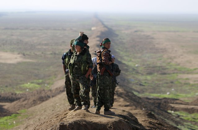 Female fighters of the Kurdish People's Protection Units (YPG) stand near the border between Syria and Iraq, close to the Iraqi town of Snoun December 22, 2014. On Sunday, Kurdish and Yazidi fighters battled to take the Sinjar back from Islamic State after breaking a months-long siege of the mountain above it. (Photo by Reuters/Stringer)