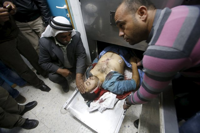 A relative touches the body of a Palestinian man who was killed by Israeli undercover forces during a raid at Al-Ahly hospital in the West Bank city of Hebron November 12, 2015. Israeli undercover forces raided a hospital in the West Bank on Thursday and shot dead a Palestinian during an operation to detain another man suspected of carrying out a stabbing, the Palestinian health ministry and doctors said. (Photo by Mussa Qawasma/Reuters)