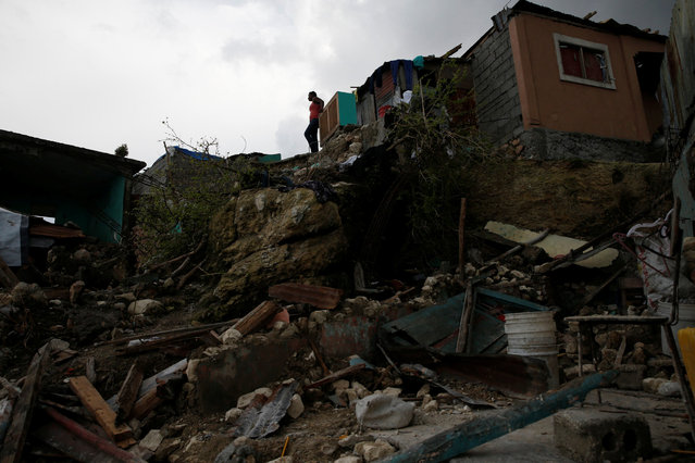 A woman stands next to destroyed houses after Hurricane Matthew hit Jeremie, Haiti, October 17, 2016. (Photo by Carlos Garcia Rawlins/Reuters)