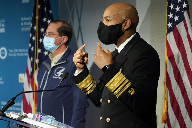 U.S. Surgeon General Dr. Jerome Adams talks about the need to still wear face masks as he speaks at George Washington University Hospital, Monday, December 14, 2020, in Washington, as Health and Human Services Secretary Alex Azar listens. The two spoke before watching COVID-19 vaccines being administered. (Photo by Jacquelyn Martin/AP Photo/Pool)