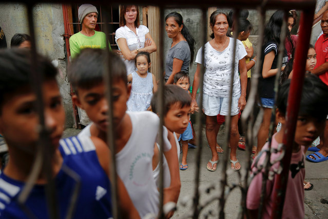 People gather outside a house where two men were killed during a drugs related police operation in Manila, Philippines October 19, 2016. (Photo by Damir Sagolj/Reuters)