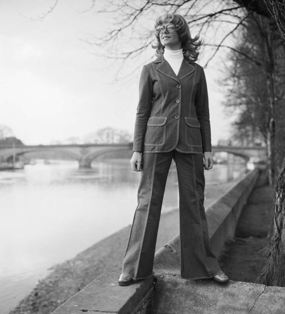 A woman stands confidently on the banks of a river, sporting a flared denim suit over a white polo-neck jumper. 27th February 1974. (Photo by Chaloner Woods/Getty Images)