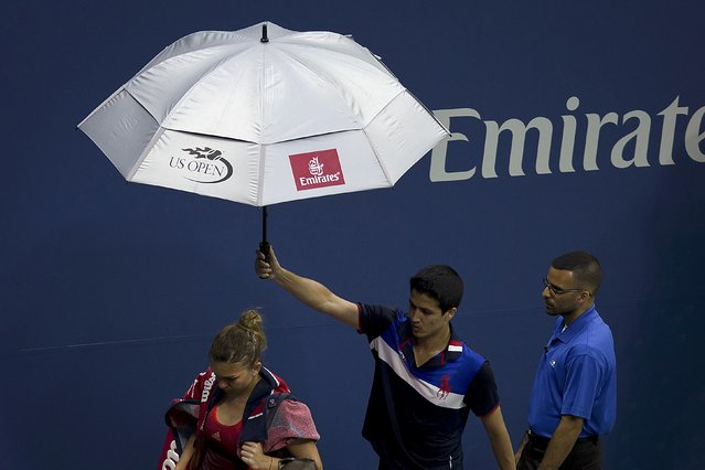 Simona Halep of Romania is escorted off the court during a rain delay in her quarterfinals match against Victoria Azarenka of Belarus at the U.S. Open Championships tennis tournament in New York, September 9, 2015. (Photo by Carlo Allegri/Reuters)