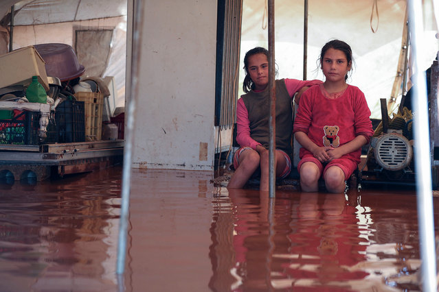 """Two girls sit inside a flooded tent at the flooded """"Mukhayyam al-Khair"""" camp near the village of Kafr Uruq in the north of Idlib province on December 17, 2020, housing Syrians displaced from Saraqib and Maaret al-Numan, and following heavy rain in the previous days. (Photo by Omar Haj Kadour/AFP Photo)"""