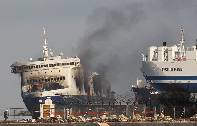 Smoke rises from the Norman Atlantic multi-deck car-and-truck ferry docked at Brindisi harbour, after a fire broke out on it off the coast of Greece January 3, 2015. Tug boats hauled the burnt-out hulk of the ferry that caught fire on Sunday off the coast of Greece into a southern Italian port on Friday, opening the way for an investigation into the cause of the blaze that killed at least 11 people. (Photo by Ciro De Luca/Reuters)