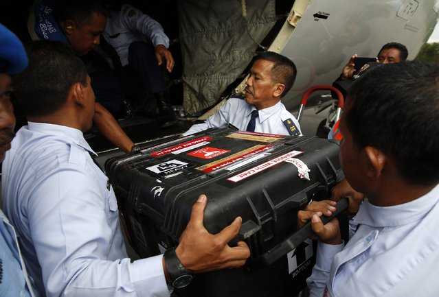 An Indonesian Air Force flight crew lift a case containing the flight data recorder from AirAsia QZ8501 onto a military plane for transport back to Jakarta at the airbase in Pangkalan Bun, Central Kalimantan January 12, 2015. (Photo by Darren Whiteside/Reuters)