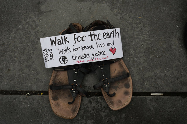 """A message saying 'Walk for the earth' is seen on a pair of shoes, as hundreds of pairs of shoes are displayed at the place de la Republique, in Paris, as part of a symbolic and peaceful rally called by the NGO Avaaz """"Paris sets off for climate"""", Sunday, November 29, 2015. (Photo by Laurent Cipriani/AP Photo)"""