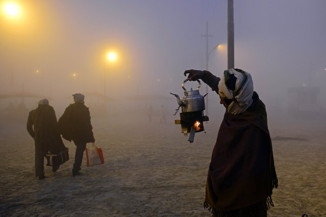 "An Indian chai (tea) vendor tends to the flame of his portable stove for his kettle as devotees return after taking a holy dip for the Makar Sankranti festival during the annual ""Magh Mela"" gathering at Sangam, the confluence of the rivers Ganges, Yamuna and the mythical Saraswati, during a cold and foggy morning in Allahabad on January 14, 2015. (Photo by Sanjay Kanojia/AFP Photo)"