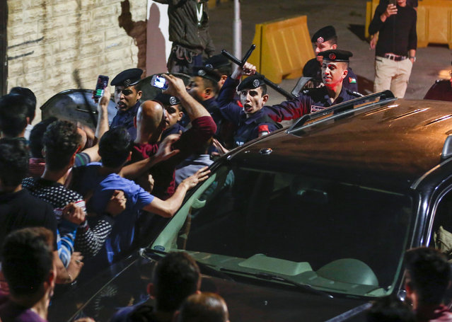 Jordanian riot police and security forces scuffle with protesters attempting to breach the area as they stand guard during a demonstration outside the Prime Minister' s office in the capital Amman late on June 2, 2018. Hundreds of Jordanians demonstrated in the capital Amman for a third consecutive day on June 2 against price hikes and an income tax draft law driven by IMF recommendations to slash its public debt. (Photo by Khalil Mazraawi/AFP Photo)