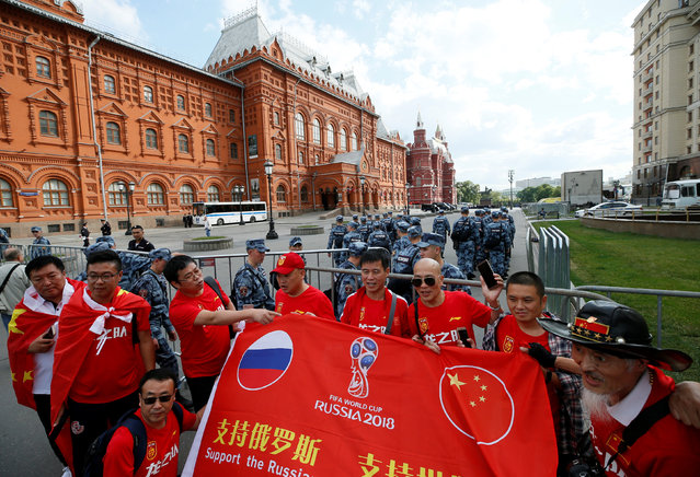 Chinese tourists pose for a picture near barriers, erected by officers of the Russian National Guard, on the eve of the 2018 FIFA World Cup in central Moscow, Russia June 13, 2018. (Photo by Gleb Garanich/Reuters)